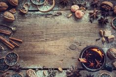 #Mulled wine and ingredients.  Mulled wine in black rustic mug with spices and ingredients on wooden background. Top view flat lay. Retro toned photo. Copy space for your text.