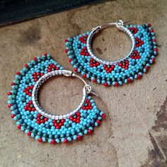 Boho beaded hoops inspired by native american beadwork - the teal, blue and red combo is great for the Christmas season with its traditional red and green color scheme.  Using the brick stitch technique, I wove tiny seed beads around the perimeter of these sturdy little silver plated hoops, using nymo thread, a strong multifilament thread favored by bead artists. The beadwork on these earrings will not flop around as I use a firm tension in my weaving, but it is slightly flexible. Store your…