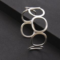 """Modern silver bracelet, handmade sterling cuff of 7 cushion shapes artisan formed and forged - """"Seven Stars Cuff"""". $80.00, via Etsy."""