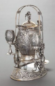 68115: A MERIDEN BRITTANIA CO. SILVER-PLATED TILTING ice water pitcher : 3 cherubs flanking holder