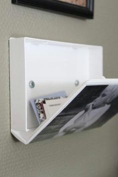 Take an old VHS case, slide a photo under the film and screw it to the wall, you have a picture frame and a hidden storage space!