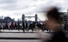 Olympics Countdown | 8 days: The Olympic rings hang from the Tower Bridge as morning commuters walk along the London Bridge. Click to see more. PHOTO BY JAE C. HONG / THE ASSOCIATED PRESS