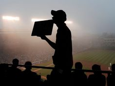 A vendor sells raffle tickets in the fog during a game between the Chicago Cubs and the Cincinnati Reds in the second inning in Chicago. The Reds won 6-2.  David Banks, USA TODAY Sports
