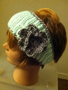 This is a super cute crocheted earwarmer. It has a fun ribbed pattern and a grey flower. It is made with soft aqua yarn and is complete with a button on the back. Cute and Warm!