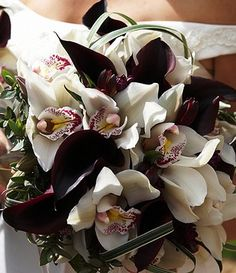 Wedding Bouquet - Simply Black and White. Deep purple almost black calla lilies complement the cymbidium orchids perfectly in this wonderful exotic bouquet.