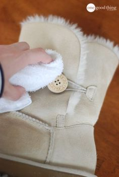 How to clean UGG Boots. If you have a water stain on one of your boots, rub the other boot against the stain. Apparently, rubbing sheepskin on sheepskin gets the stain out.