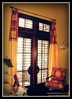 Shutters in family room with drapes