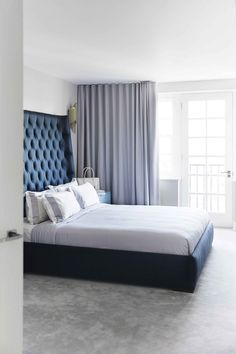 Gavl med natblå polstring, Ralph Lauren-sengetøj i lavendel/hvid - og fjernstyrede, gulvlange gardiner i toner af lavendel.