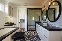 indirekte LED Beleuchtung, zwei runde Spiegel mit schwarzem Holzrahmen, weißer Waschbecken Unterschrank, schwarzer Polsterhocker vor der Einbauwanne, Boden mit kleinen schwarzen und weißen Fliesen