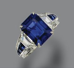 SAPPHIRE AND DIAMOND RING. The emerald-cut sapphire weighing 8.02 carats, flanked by 2 trapeze-cut diamonds, the shoulders set with baguette diamonds and calibré-cut sapphires, further accented with small round diamonds, mounted in platinum, size 6½.