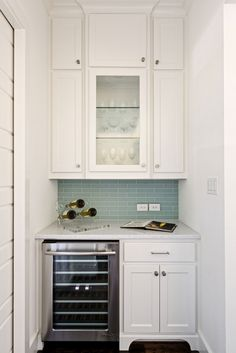 This kitchen includes some of the latest trends in both kitchen appliances and tile. This wine refrigerator cooler is a perfect addition! #dream #ideas #white