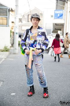 May 2015: Maro is wearing a resale jacket and comic-print t-shirt with handmade torn jeans. His see through neon backpack is from Kinji and his Union Jack boots are Dr. Martens. He embellished his cap with lots of safety pins.