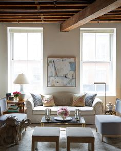 Under a ceiling accented with rustic wood beams, this gorgeous living room features a gray camelback sofa positioned beneath a white and blue abstract art piece hung between windows facing a tiered bamboo end table lit by a white lamp and a brass floor lamp positioned beside a round side table.