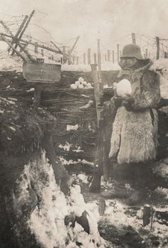 An armed German soldier wearing a gas mask posing with a sign celebrating Easter and an Easter egg snowball in a trench on the Eastern Front, 1917. [1382x2048] : HistoryPorn