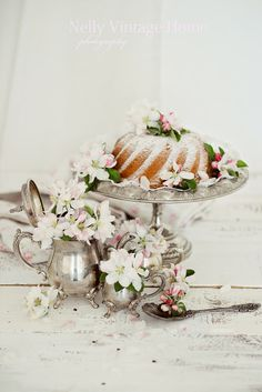 Lovely silver tea service, flowers and powdered sugar cake...