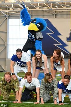 Prince Harry takes part in a cheerleading display in the American football indoor training center, at the US Air Force Academy base in Colorado Springs. Remarkably, the Prince also managed to rope in Britain's most senior military officer in the US, Major General Buster Howse, military attaché to the British Embassy in Washington, who crouched down beside him.