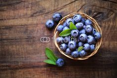 Fresh ripe garden blueberries in a wicker bowl on dark rustic wooden table. with copy space for your text