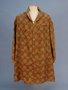1850s GENT'S REVERSIBLE WOOL PAISLEY DRESSING GOWN. Having two similar prints of differing scale in orange, gold, beige, blue and green, with collar and three purple abalone buttons. Chest 50, length 41, sleeve 22. (Some mends, lacking belt.) Whitaker Auctions. Click through for detail images.