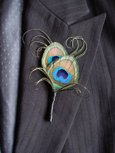 This simple elegant peacock feather boutonniere is dressed with beautiful peacock curls and a simple black satin wrap. Perfect for your peacock themed