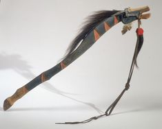 A famous Dance stick owned & made by No Two Horns (Hunkpapa Lakota), North Dakota to honour a horse that carried him to victory. The details of the dance stick show that his horse suffered 6 different wounds, shown by the red triangles, & the scalp replica attached to the horse's mouth. The eagle feather & fancy silver bridle also suggest the importance of this animal showing that it was a cherished companion. Also note the carved hoof & and the rawhide ears.