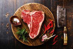 Raw meat T-bone steak and cleaver