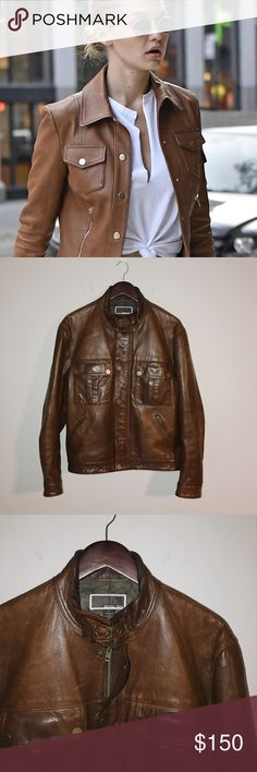 Michael Kors Brown Leather Jacket This Michael Kors jacket would be a gorgeous fall staple in your wardrobe! The warm tan leather will compliment all your outfits for the fall. This jacket has a buckle neck closure and a hidden zipper underneath a set of snap buttons. It is in excellent condition with a few scuff marks when closely examined, but unnoticeable when wearing. I took great care of this coat and only wore it out occasionally.   *disclaimer: the cover photo of Gigi Hadid is a…