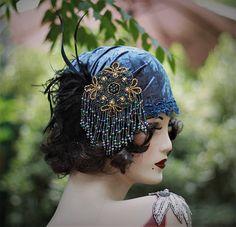 Des années 1920 de style vintage casque chapeau femmes inspiré par la mode dragueur de fille de Bohème aileron de 20 années... c'est une one-of-a-kind conception originale avec un style unique. Sa couronne est recouvert d'un velours volet en moyen foncé vieux bleu, orné de perles de fantaisie garniture autour de la Couronne. Agrémenté de plumes et d'un bijou perlé surdimensionné qui pend joliment sur le côté du chapeau. Un chapeau d'amusement à porter à n'importe quel 1920 s flapper fête ou…