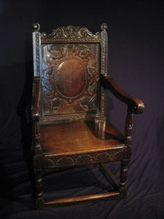 LATE ELIZABETHAN OAK WAINSCOT ARMCHAIR. C1590    A FINELY CARVED TOP RAIL ABOVE A WONDERFUL RENAISSANCE CARVED PANEL WITH OVAL CENTRAL PANEL. THE DOWNSWEPT ARMS WITH SCROLL ENDS, ABOVE FLUTED CUP AND COVER SUPPORTS. THE SEAT WITH CARTOUCHE CARVED FRIEZE WITH KNULL CARVED CORNERS. STANDING ON TURNED LEGS UNITED BY MOULDED STRETCHERS