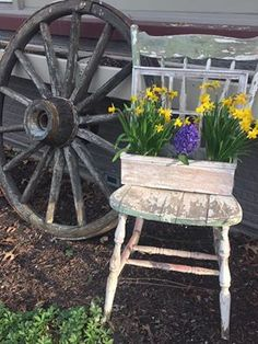 Primitive outdoor decorating. Wagon Wheel and chair with beautiful spring flowers.