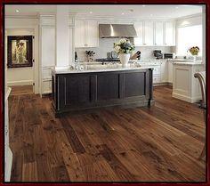 Dark island, barnwood flooring and white cabinetry #hardwoodfloor