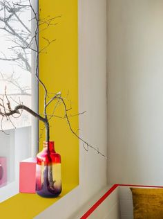 Yellow paint around window, with vase and branch