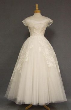 """A positively exquisite 1950's wedding gown in ivory tulle. Fitted, off-shouldered, short sleeved bodice with pleated tulle inset at the neckline. Gown has a tremendously full, triple layer tulle skirt with lace appliques (shown here with an additional crinoline... not included). Dress is lined. Rear metal zipper. """"Emma Domb California,"""" label."""