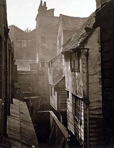 """Cloth Fair, ca.1877  Published by Society for Photographing Relics of Old London Printed by Henry Dixon & Son.  ""Cloth Fair, though it has undergone alterations in recent years, still preserves, far beyond any other portion of London, mediaeval characteristics. There are here narrow walled lanes, where two persons can pass one another with difficulty. In another lane the occupants of the houses could literally, and without danger or difficulty, shake hands from the windows on opposite…"