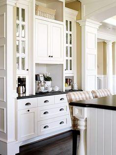 white cabinets, dark counters, gold/yellow walls, dark hardware