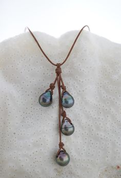 """Offering styles both casual chic for a day at the beach, and elegant edge to flaunt for cocktails and more. Not your mother's traditonal strands of pearls each signature design is hand-crafted and strung on soft, hand-rolled leather and tied with precision and care. The """"Offset Rain"""" necklace by designer Wendy Mignot. #tahitianpearls"""