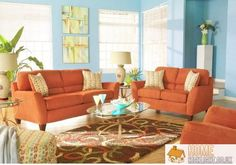 ... walls with green canvas art provide the perfect backdrop for the hardwood floors and comfy orange sofa set with a lovely brown rug to complete the room.