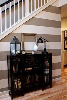 PAINT WITH THE PRIMARY COLOR FROM LIVING ROOM AS ONE OF THE STRIPES TO SET OFF FOYER AREA, BUT NOT USE A DIFFERENT COLOR SCHEME