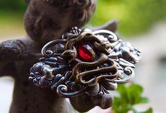 Barrette à cheveux (8cm de largeur) composée de plusieurs estampes en métal vieilli. Deux serpents enserrent un cabochon de verre à facettes rouge (18x13mm). Les serpents sont posés sur une large...