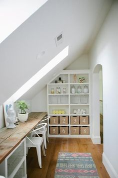 Fantastic craft room features a sloped ceiling fitted with skylights over a reclaimed wood plank desk lined with white metal chairs alongside a built-in bookcase filled with numbered bins and Imm Living Coiled Cobra Wall Hooks. Attic Rooms, Attic Spaces, Small Spaces, Kid Spaces, Tiny House, Loft House, Built In Desk, Built In Bookcase, Bookcase Shelves
