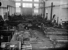 Crichton-Vulcanin korkeakattoisessa telakkahallissa otetussa kuvassa välittyy työn vilinä. Liikkuvat työmiehet ovat tallentuneet kuvaan haamumaisen läpinäkyvinä. Monet ovat kuitenkin pysähtyneet katsomaan kameraan kuvanottohetkeksi.  Turun suurimman laivatelakan Crichtonin juuret yltävät 1730-luvulle saakka, jolloin Sotalaisten kylän eli nykyisen Urheilupuiston maalle perustettiin pieni laivaveistämö. Vuonna 1874 yhtiön nimeksi tuli W:m Crichton & C:o Ab, kun tehtaan omistajaksi tullut…