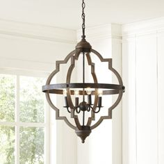 Two quatrefoil frames interlock to give the Bennington Chandelier a unique, striking look that's accompanied by metal banding and a turned decorative finial. The oak finish and candelabra-style fixtures make it a lighting choice with rustic charm to spare.