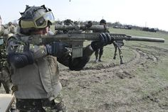 A Romanian soldier assigned to the Romanian Land Forces tries out an M110 semi-automatic sniper system during a display by troopers assigned to 2nd Squadron, 2nd Cavalry Regiment, showing the weaponry that they are assigned and use while training, after participating in the opening ceremony for Wind Spring 2015 at Smardan Training Area, Romania, April 16, 2015.