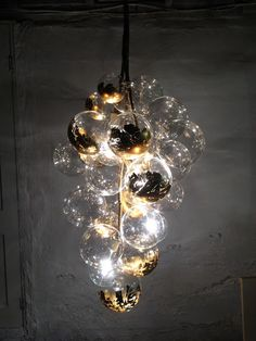 One of a kind lighting made to order. An organic, waterfall shaped chandelier made with hand-blown glass bubbles in mixed 4 and 6 sizes. By day