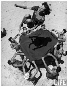 Teenage boys using blanket to toss their friend, Norma Baker, into the air on the beach (1948).