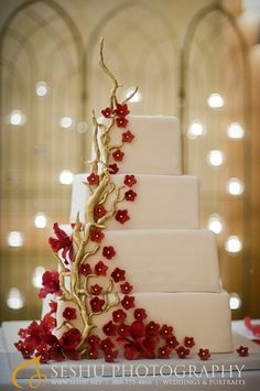 Wedding cakes - Square stacked wedding cake with gold branches, deep red blossoms and orchids.
