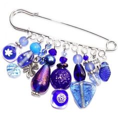 Donkerblauwe grote speld broche met diverse mooie glaskralen.
