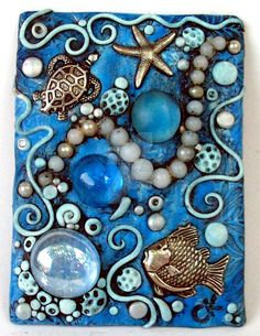 An ACEO I made from polymer clay with glass gems, a solid brass mermaid and shell. All of the little corals, shells and such were made of clay. I gave it a wash of acrylic paint to bring out the de...