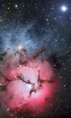 The Trifid Nebula, 5,200 light years from Earth, is an unusual combination of an open cluster of stars, an emission nebula (a cloud of ionised gas emitting light of various colours), and a dark nebula (a type of interstellar cloud that is so dense that it obscures the light from the emission nebula).