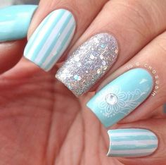 Light blue nails with white stripes, silver confetti/tinsel glitter nail and light blue nail with white floral design and crystal.