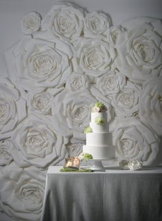 """White paper flower wall: Flower-covered walls are the next big thing in wedding flower décor. And why not? This idea pulls double-duty as both a ceremony and photo booth backdrop. It's also a great way to bring the outdoors in if you're saying """"I do"""" in a ballroom setting."""